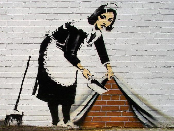 banksy_graffiti_mujer_levantando_pared_ladrillos